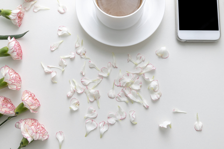 Flat lay of Coffee in white cup with pink and white carnation flowers and petals with smart phone on white desk. Top view.