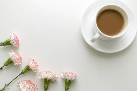 Coffee in white cup with pink and white carnation flowers on white desk. Top view.