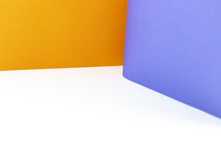 Abstract orange and purple color papers background on white table. Фото со стока
