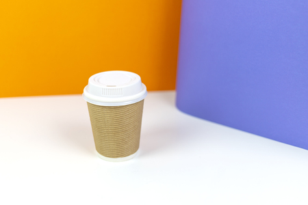 Coffee paper cup with colorful  orange and purple background. Stock Photo