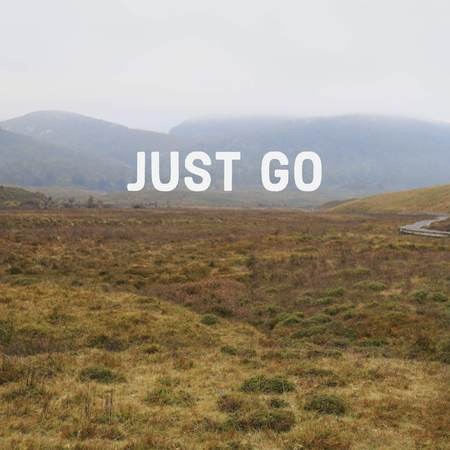 Inspirational motivational quote Just Go on mountain background.