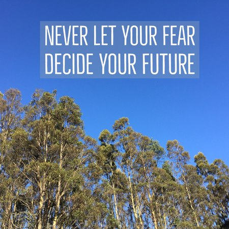 Inspirational motivational quote never let your fear decide your future. with trees and blue sky background.