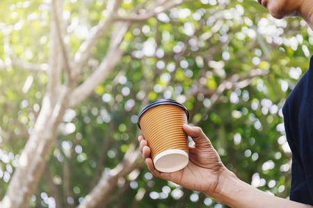 Close-up of male hand holding a paper cup of coffee to take away.