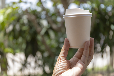 Close-up of male hand holding a white paper cup of coffee to take away in sunny day.