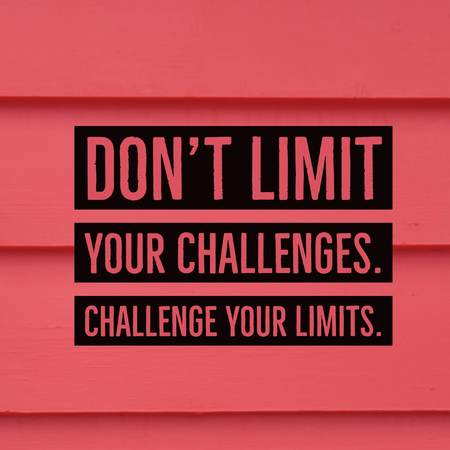 Inspirational motivational quote Dont limit your challenges. Challenge your limits. on red wooden wall background.