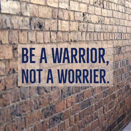 Inspirational motivational quote Be a warrior, not a worrier. on beautiful brick wall background.