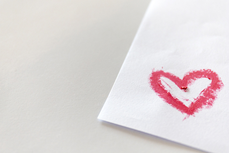 Pink lipstick smeared in heart shape on white paper on white table.
