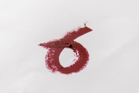 Red lipstick smeared on white paper. Top view. Stock Photo