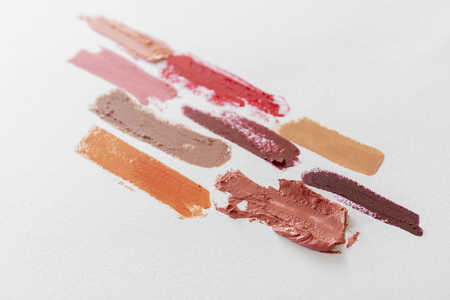 Colorful lipsticks smeared on white paper. Top view.