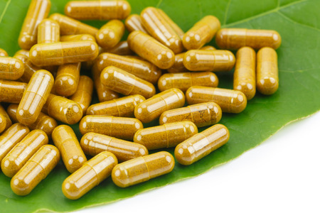 Turmeric Powder in Transparency Hard Gelatin Capsules with Green Natural Leaves on White Background.