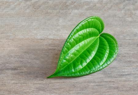 Shaped green betel leaf heart shape on wood