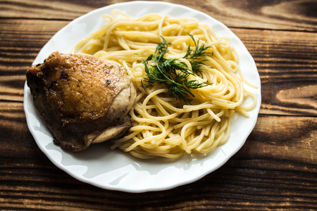 plate with spagetti and fried chicken thighs Stock Photo
