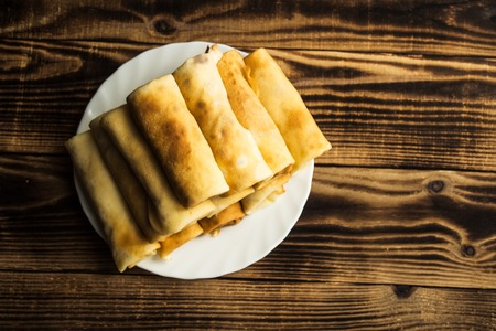 blini: stuffed crepe stacked on white plate wooden background