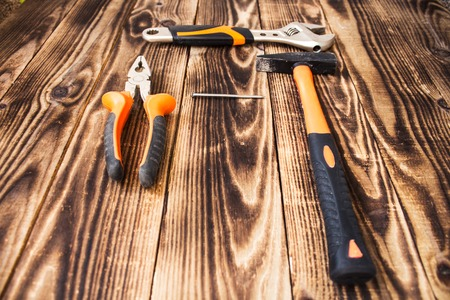 adjustable: a pliers hammer nail and adjustable wrench Stock Photo