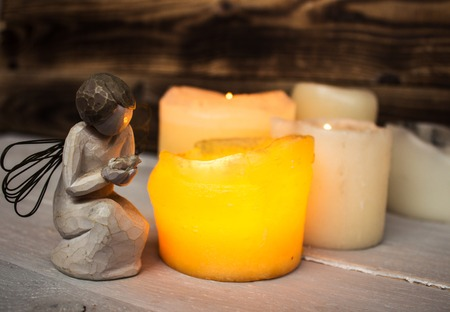 stone angel and candle light on wooden background