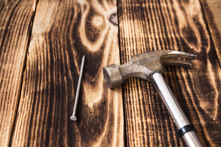 pounding head: nail and a hammer on wooden background Stock Photo