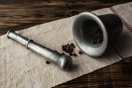 cooking utensils: a mortar and pestle with whole pepper Stock Photo