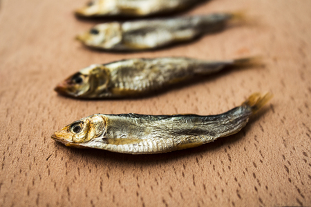 sardine can: a little smoked sprats on wooden background