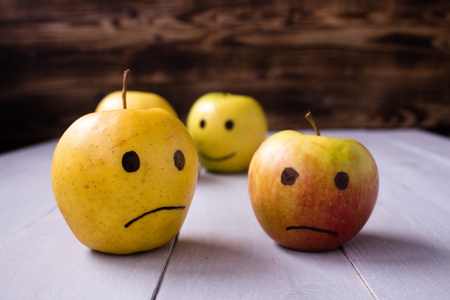 yellow apples with drawn emotions on wooden background