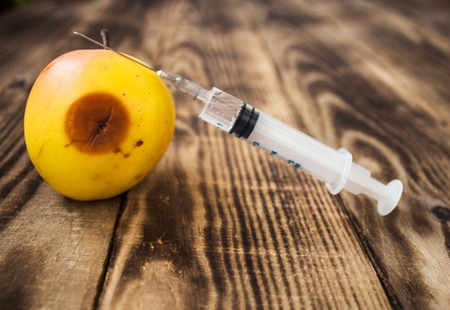 yellow apple with rot and syringe on wooden background Stock Photo