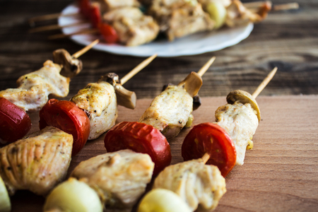 chicken shish kebab with tomato and mushroom barbecue on wood Stock Photo