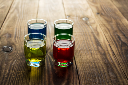blue yellow green red alcohol shot drinks on wooden background