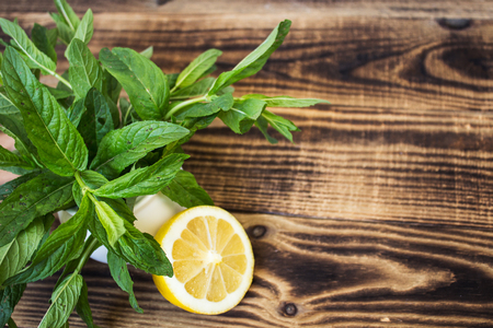 small white vase with fresh mint and lemon on wooden background Stock Photo