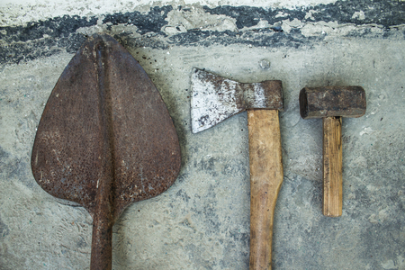 a Rusty ax hammer and shovel on a white background
