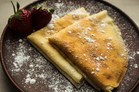Pancakes crepe with strawberries and powdered sugar Stock Photo