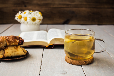 bible and tea daisies croissants on wooden background Stock Photo