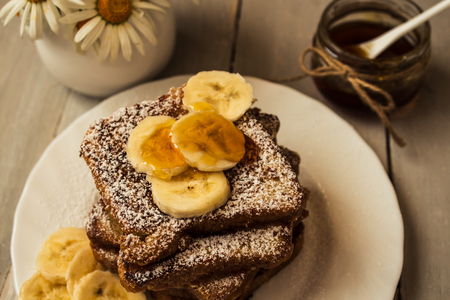 french toast with bannana and honey on wooden background