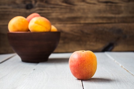 bowl of ripe apricot on a wooden background summer