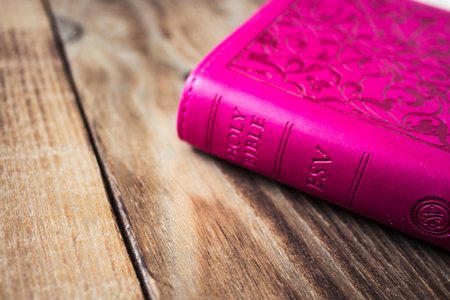 a pink closed bible on wooden background