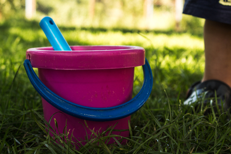water bus: pink baby bucket and blue shovel on the grass Foot of a child
