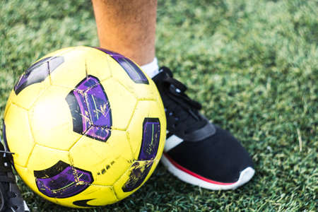 the feet of man in sneakers and soccer ball on a field