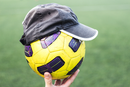 a Soccer ball on a hand in a cap Stock Photo