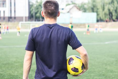 Un uomo che tiene una palla di calcio sul campo Archivio Fotografico - 83656244