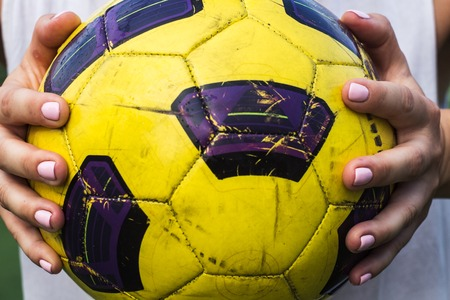 a woman holding a soccer ball in her hands
