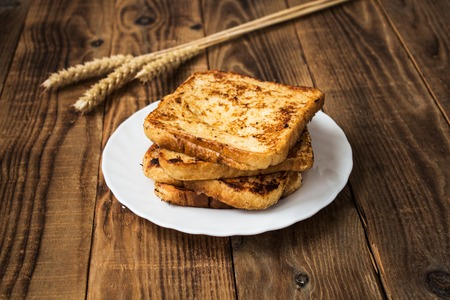 a stack of french toast with spikelet on wooden background