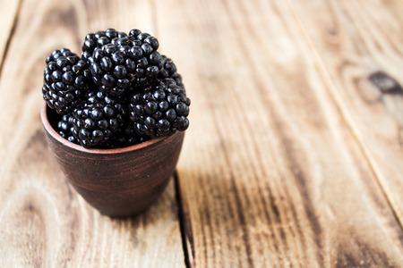 Ceramic plate with blackberry on wooden background Standard-Bild