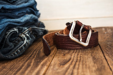 stack of jeans on a wooden background and a belt