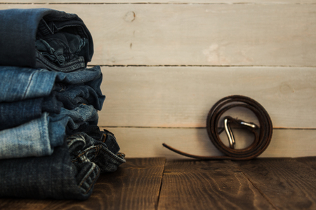 A stack of jeans on a wooden background and a belt