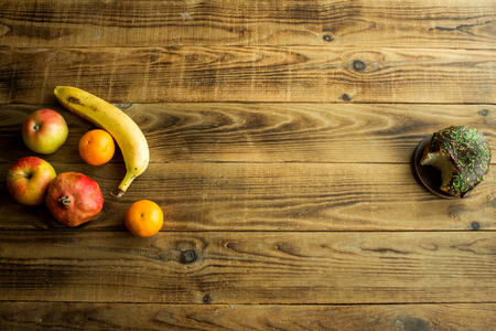 fruit and donut with chocolate on a wooden background