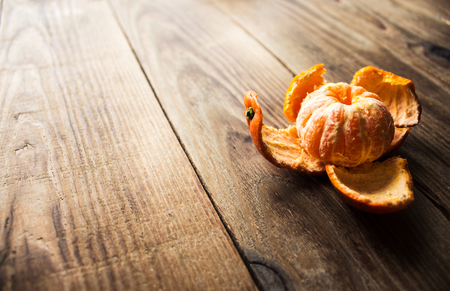 a peeled mandarin on a wooden bacground