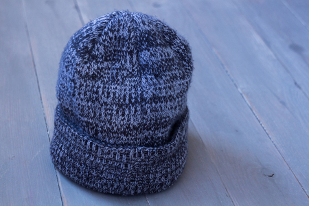 a gray winter warm hat on a wooden bacground