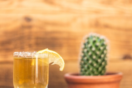 a Tequila with lemon and cactus on a wooden background Stock Photo
