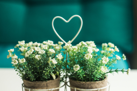 a vase with wildflowers and heart on the table