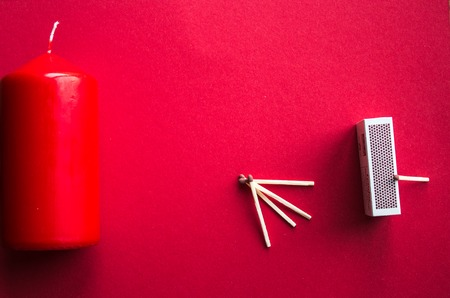 a candle and matches on a red background