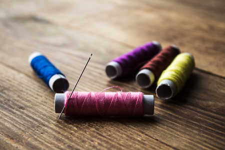 a sewing thread on a wooden background Stock Photo