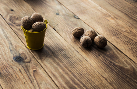 a nuts in a small bucket on a wooden background